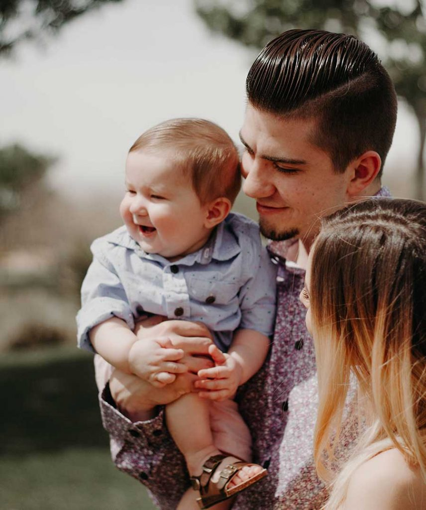 A young man and woman hold thier small child in their arms