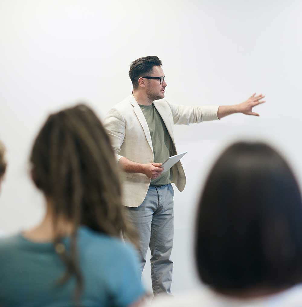 A teacher presents at the front of a classroom of adult students